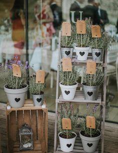 plan de travail pour mariage original en pots de lavande avec des listes invités accrochées à des bâtonnet en bois, lanterne vintage décorative, coeurs noires