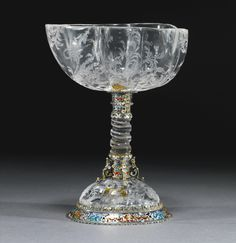 A rock crystal cup on a spiral stem with enamelled silver mounts, probably Vienna, late 19th century the polylobed oval cup and domed base engraved with scrolling foliage, flowers, birds and insects, the silver mounts, apparently unmarked, with enamelled arabesques, applied with male caryatid brackets
