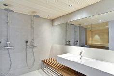 Light grey walls. Faucets: wash basin faucet Il Bagno Alessi One by Oras, shower faucets Oras Cubista thermostats with Oras Hydra rain shower sets.