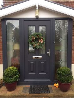 This dark front door framed by stained glass is an elegant way to open up your home by expanding on the windows. The dark door accents the brick house and plants add a necessary touch of green. Porch Windows, Front Door Porch, Grey Front Doors, Porch Doors, Front Porch Design, House Front Door, The Doors, House With Porch, Entry Doors