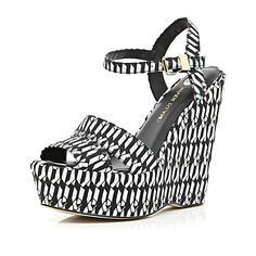 Get your spring looks in top shape with these black and white geometric print canvas wedge sandals.