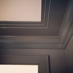 ceiling and crown moulding blend seamlessly into painted wood paneling