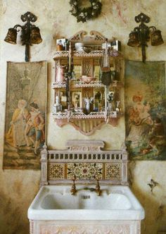 Incredible bathroom sink area with Moroccan tiles, antique paintings and vintage wall lights - very bohemian