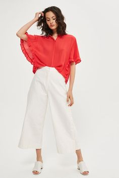 In airy red fabric, this short-sleeved boxy shirt comes with frilly sleeve edges for a pretty touch. It's perfect for complementing culottes and cropped trousers.
