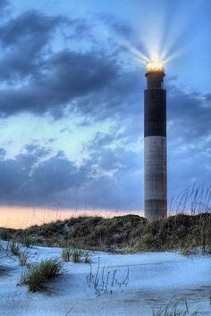 Caswell Beach North Carolina as the Oak Island Lighthouse shines its warning of shallow wate by jc findley Nc Lighthouses, North Carolina Lighthouses, North Carolina Homes, Oak Island North Carolina, Southport North Carolina, Oak Island Lighthouse, Nc Beaches, Carolina Beach, Carolina Usa