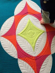 The little foot shows the proportions of this quilt. Beautiful machine quilting.