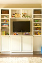 The design associates in the Lowe's kitchen cabinetry department created a custom entertainment center by mixing base cabinets with open shelving and beaded-board panels. The finished result is a timeless piece that offers plenty of storage for books, video games and movies.