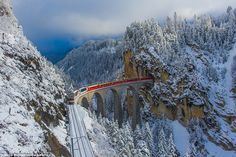 Rolling across a 213-foot-high viaduct in the Alps, the red carriages of the Bernina Expre...