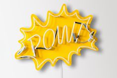 """A NEON SIGN THAT READS """" POW."""" IT HAS A YELLOW BACKGROUND, BUT THE LETTERS ARE WHITE."""