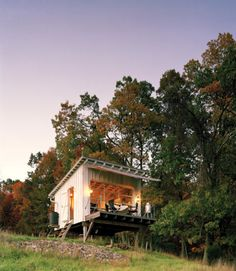 Designed by Broadhurst Architects, The Shack at Hinkle Farm sits on a mountain in West Virginia. With no electricity, the family relies on oil lamps for light and a wood stove for heat; rain water is collected from the roof for the outdoor shower. An aluminum and glass garage door opens to a cantilevered wooden deck, where a removable canvas awning offers shade and shelter. Can you imagine the view from that deck? | Tiny Homes