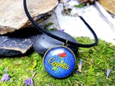 This elegant choker is fit for a princess. A bronze personalized pendant holds the name of your choice in pretty yellow font over a damask blue background and red rose. Its set with a glass dome over the pendant. Set on a 10 inch black leather cord and two inch bronze extender with