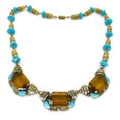 A beautiful Czech necklace in an unusual blue and yellow colour way. The necklace features beautiful metal panels set with faceted glass stones....