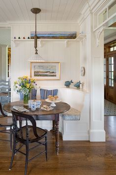Small Shingle Beach Cottage - Breakfast nook. Blue & white liberty-style fabric on the bench seat & bold stripe on the pillows along with the white walls create a refreshing mood. Nice accents with the ceramics and cane seat chairs.