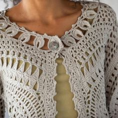 A layer as gentle as a spring breeze, pretty as the first blossoms. Hand crocheted blend of a linen/cotton. Shell button. Cropped length; 3/4 sleeves....