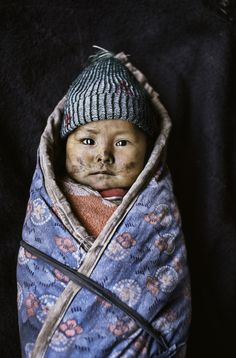 stevemccurrystudios:  Today's photograph pictures a baby bundled against the cold in Xigaze, Tibet.  Current Museum Exhibitions Museum für ...