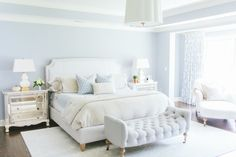 White and blue bedroom features tray ceiling accented with Barbara Barry Simple Scallop Pendant over blue walls framing an ivory linen bed with nailhead trim dressed in ivory and blue bedding flanked by French mirrored nightstands topped with Anita Table Lamps alongside a tufted bench on caster legs placed at the foot of the bed atop a white rug layered over oak hardwood floors.