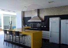 Do lado externo da residência, o espaço gourmet recebeu o mesmo padrão de armários da cozinha, mas conta com materiais diferenciados, como a bancada amarela com acabamento glossy e o mosaico de pastilhas de vidro que combina tons de cinza e prata, lindo e sofisticado.
