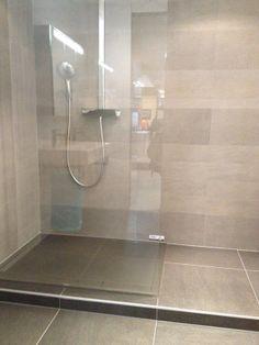 De kracht van eenvoud: glazen open douchewand en grote tegels aan de wand en op de vloer.