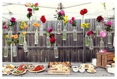 Old glass milk bottles with flowers in them and hanging by the fence.