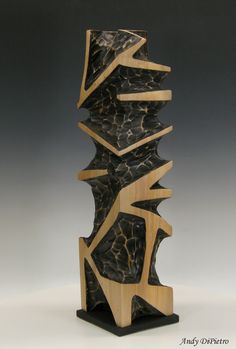 Geometric sculpture carved from Silver maple 24x6x6 dyed black with lacquer finish.