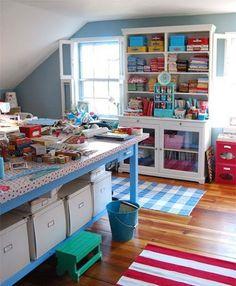 Taller de costura con estante para las telas y cajas. Mesón cajas y elementos de costura, en la bandeja del mesón cajas blancas como organizadoras.