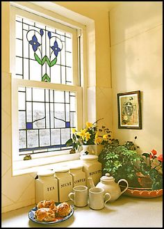 Stained glass window in warm yellow kitchen.