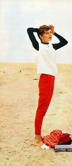 Audrey Hepburn, red skinny jeans, black and white flowy top on the beach. Summer casual.