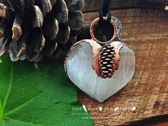 Selenite heart with a tiny embedded cone in antique copper.  Very happy with this one!!!  Available now.  www.leafseedpodshell.com #leafseedpodshell #leafseedpodshelljewelry #birdhouse #leaves #leaf #acorn #acorns #seeds #pods #shells #copper #electroform #electroforming #electroformed #electroplated #electroplating #crystal #crystals #rustic #plating #jewelry #jewellery #pendant #pendants #handmade #handmadejewelry