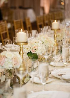 Glamorous table setting with beautiful low centerpieces and candles. Beaver Creek Colorado Wedding