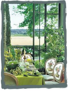 Green dining room with a view in the home of Ginny Magher, an Atlanta-based interior designer who bought and restored an ancient farmhouse in Provence with Lafourcade Architects