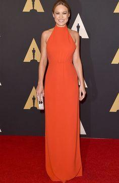 Look de Brie Larson no red carpet com vestido laranja liso.