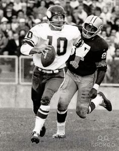 Minnesota Vikings quarterback (10) Fran Tarkenton scrambles from Green Bay Packers defensive end (87) Willie Davis at Lambeau Field.