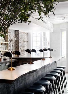 a row of leather stools, free form natural wood bar surface, exposed brick wall, double apothocary lamps at  MUSKET ROOM / NEW YORK