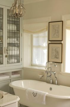 Vintage fixtures and a roll-top pedestal bath tub set the traditional tone of this soothing and elegant principal bathroom. ~built-in cabinets as storage for linens, recycling old leaded windows from elsewhere in the house to create the doors. ~off-white palette and Roman shades create a soothing ambiance while art and an antique chandelier complete the look.