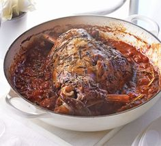 Herby baked lamb in tomato sauce. Cook this 'low and slow' in its own sauce til it's so tender you can carve it with a spoon...