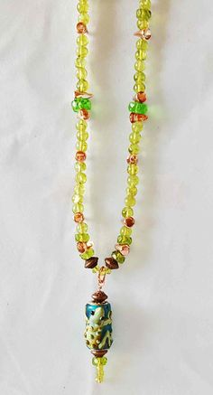 """Glass & bead 19"""" necklace, frog focal bead, stylish fun necklace, green, blue, copper, glass beads, faceted peridot beads, brass closure. by LizHivelyJewelry on Etsy"""
