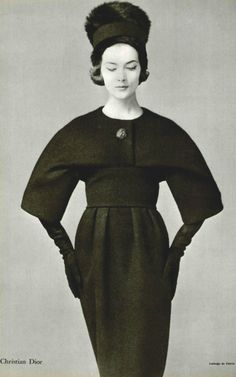 1958 Rose Marie is wearing wool dress with curved line that defines the shoulders and wide high waistband, by (Yves Saint Laurent) Christian Dior