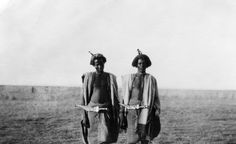 Portrait of two AFAR (Asaimara Danakil) warriors, standing, wearing knives across their waists from which hang leather tassels denoting how many men each has killed. The man on the left is Hamdo Ouga, a young Asaimara chief who was killed by warriors of the rival Adoimara Danakil tribe a few days after this photograph was taken. Copyright Pitt Rivers Museum, University of Oxford