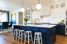 This is a kitchen a chef would love, with tons of counter space and a kitchen island for preparing and gathering guests. White countertops, stools, upper cabinets and backsplash keep the space looking simple and clean, while navy blue lower cabinets and kitchen island give the kitchen a crisp, nautical feel. Globe fixtures provide tons of light and a modern touch.