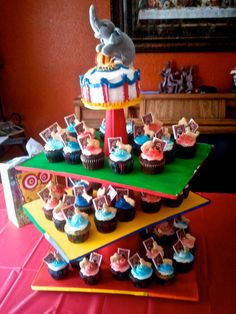 Circus cupcake stand & smash cake. couldn't find a stand to hold 50 cupcakes so I made one with a styrofoam cone and cake boards painted and glued ribbon around edges