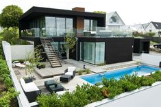 Beautiful modern home with pool, black paint, staircase and glass railing designed by Villa Nilsson. Homesandlifestylemedia.com #architecture #modern #glass #minimalistic #home #house #design #sleek