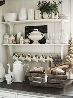 Love the rustic look in this kitchen.  The open shelves, white painted wood walls, and tone on tone white finishes.