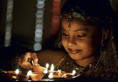 Credit: Sanjeev Gupta/EPA An child lights earthenware lamps on the eve of Diwali in Bhopal, India