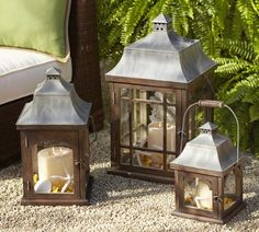 wood-and-metal lanterns feature stately mansard roofs and distinctive architectural details. Tall wire bales make them easy to carry or hang.
