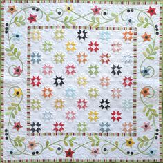 """Charming pieced stars from lots of colorful fabrics dance across a crisp white background. The appliqued border also uses stars and make this a stunning quilt. Finished Size: 56"""" x 56"""""""