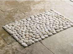 """Smooth river stones in neutral tones add natural beauty and functional appeal to a mat that can be used next to a door or beside a shower.  Each is unique, wonderfully tactile under foot, and artfully composed, as in a mosaic. 20""""W x 29.5""""L.   $49"""