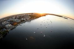 Boats dot Lake Mendota in a fisheye-lens aerial view of the University of Wisconsin-Madison campus during an autumn sunset on Oct. 5, 2011. Major campus facilities pictured along the shoreline, from left to right, include the Pyle Center, Below Alumni Center, Armory and Gymnasium (Red Gym), the Memorial Union Terrace, Helen C. White Hall and Picnic Point. The photograph was made from a helicopter looking southwest. (Photo by Jeff Miller/UW-Madison)