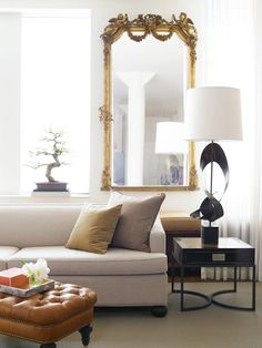 {The living room features a gilded, Baroque mirror along with a clean-lined sofa stretched to a 12ft length, statement-making lamps and end tables along with a handsome, tufted ottoman in cognac leather with brass nailhead trim.}