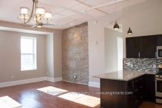 Unit #3 Living Room. Open concept, restored maple flooring, exposed granite wall.