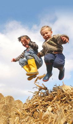 Kids at Play by Joe Murphy - Two children leap from a bale of cornstalks on their rural Iowa farm.